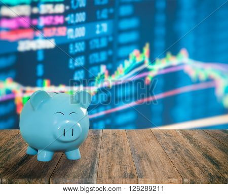 Blue Pig Bank On Wood Background With Blur Stock Market Background,money And Saving Concept.