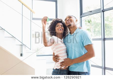 Happy couple embracing and showing house key in their new home