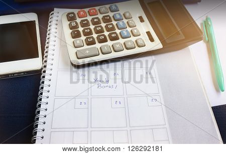 Organiser Book With Text Yearly Bonus And Background Of Calculator And Cellphone In Dim Light Room