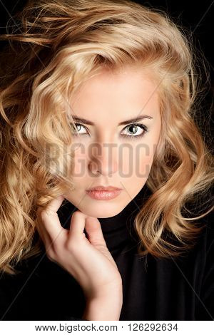 Beautiful blonde woman with stunning eyes over black background. Beauty, fashion. Make-up, smoky eyes.