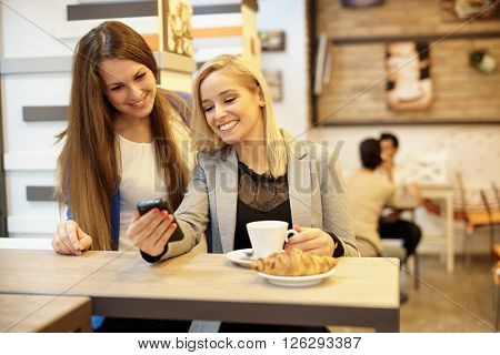 Happy girls using mobile in cafeteria.