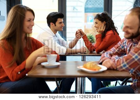 Romantic couples having a date in cafeteria.