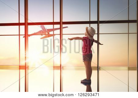 Cute little child girl looks at a plane at the airport.