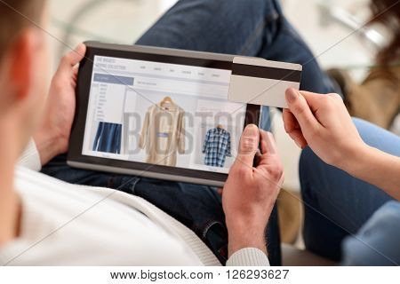 Online purchase. Selective focus of credit  card  and tablet in hands of nice couple and  sitting on the couch while doing shopping