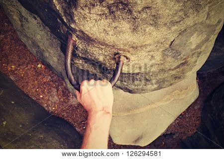 Rock Climber's Hands On Steel Handhold Anchored In Sandstone Rock. Tourist Path Via Ferrata.