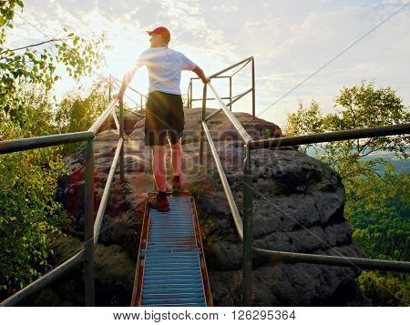Tired Hiker Keep Handrail On Peak. Sunny Spring Daybreak In Rocky Mountains. Hiker With Red Baseball