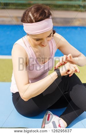 Young Sporty Woman Using Fitness Wristband Watch