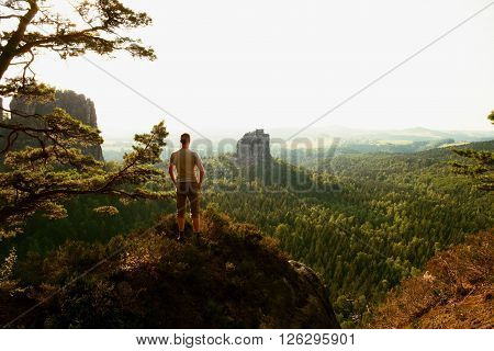 Tall Tourist Climbing On Sharp Cliff And  Overlooking Beautiful View Above Forest Valley Bellow.