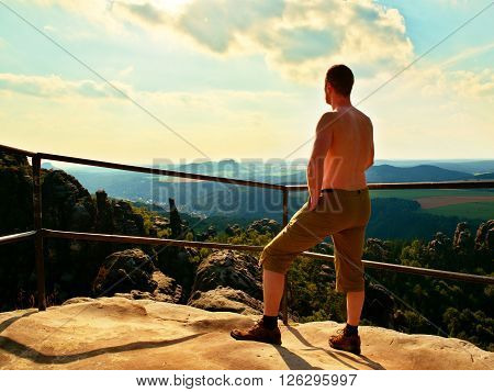Short Hair Naked Tourist At Handrail On The Peak Of Sandstone Rock Watching Into Landscape. Hot Summ