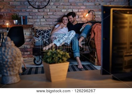 Young loving couple watching tv at home, embracing.