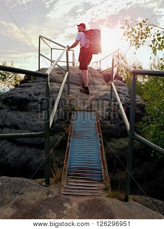 Tall  Backpacker Hold Handrail On Rock. Sunny Daybreak In Rocks. Hiker With Big Backpack, Baseball C