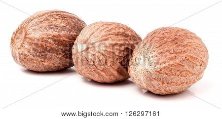 Three nutmeg whole isolated on white background.