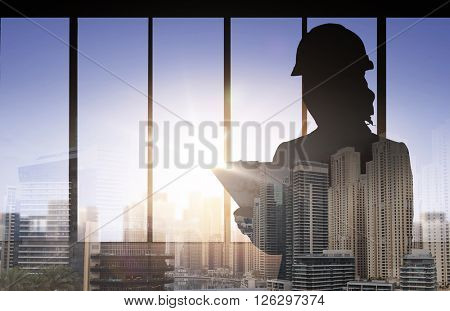 business, building, industry and people concept - silhouette of woman in helmet with clipboard over double exposure office and city background