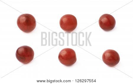 Six single dark red grapes isolated over the white background