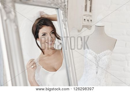 Beautiful young bride looking at herself in mirror while trying on veil on wedding-day.