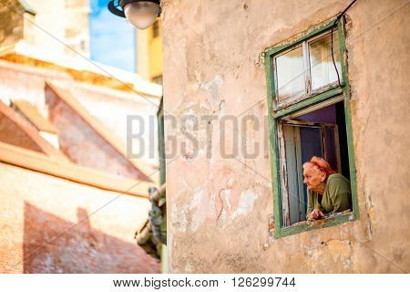 SIBIU, ROMANIA - CIRCA JUNE 2015: Elder woman looks out the window in old building in Sibiu old town in Romania. Life on pension in Romania