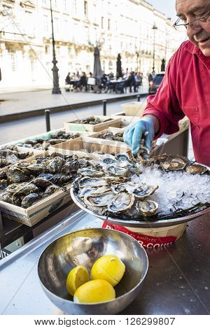 Bordeaux France - March 26 2016. Cook selecting plate up and selling a tray of opened fresh oysters on a shell and on ice with lemon in a street of Bordeaux capital of Aquitaine. France.