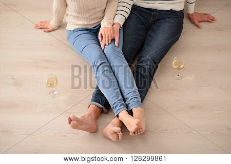 Find inspiration. Top view of pleasant loving couple holding hands of each other and sitting on the floor while resting