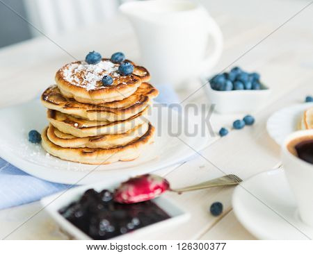 pancakes with blueberry and jam on white wooden table