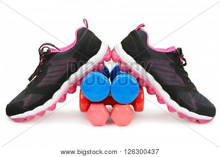 pair of sneakers and dumbbells isolated on white