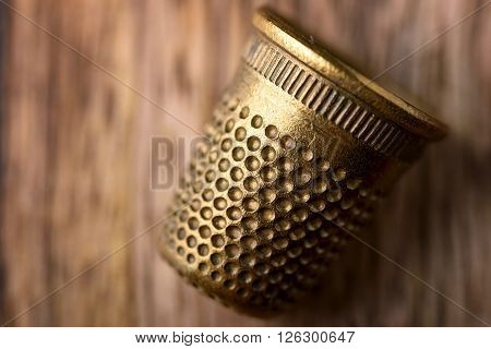macro of brass thimble on wood for sewing
