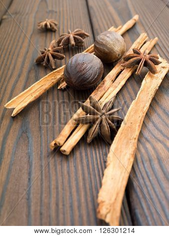 Star anise whole nutmeg and cinnamon sticks on the dark textured wooden background