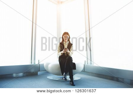 Young confident Japanese woman sales manager is reviewing the state of bank account by using internet banking on mobile phone while is sitting in company where she work against window with copy space