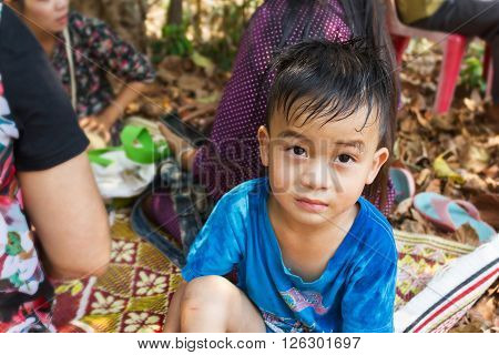 Cute Asian boy sitting under tree shade among people and looking at camera