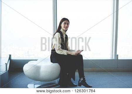 Young Chinese successful woman with mobile phone in hands is smiling for the camera while is sitting in modern office. Hipster girl using cellular while waiting for flight departure in airport hall