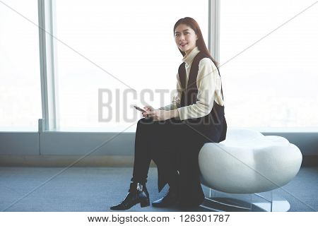 Cheerful Asian hipster girl with trendy look is holding mobile phone in hands and smiling for camera while is sitting in loft luxury apartment. Chinese entrepreneur of financial company using cellular
