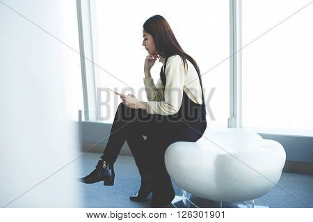 Young confident Chinese woman is searching information via cell phone about financial newswhile is waiting beginning of the conference with international partners during her business trip to New York
