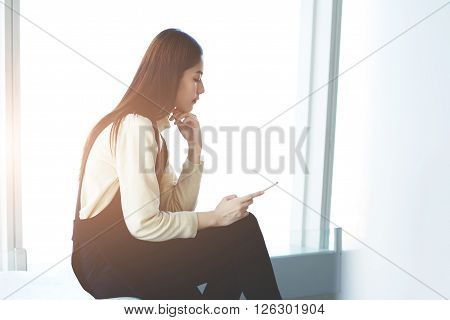 Asian woman intelligent CEO is reading electronic book via cell phone about personnel management while is sitting in airport hall before her business trip to New York. Concept of using mobile devices