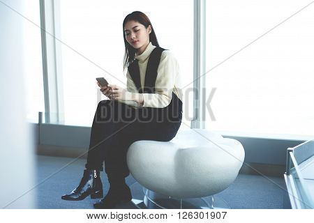 Young atrractive Japanese woman is checking the status of account by using obline internet banking on mobile phone. Asian female is waiting for car in airport what she ordering on-line for the trip