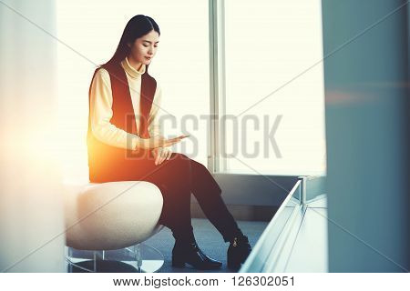 Asian female office worker of successful company is networking via application on smart phone. Woman is chatting via cell phone while is waiting plane departure in contemporary airport interior