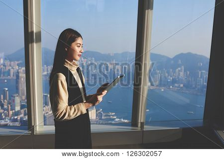 Young Chinese woman proud managing director is using portable digital tablet for summarizing the results of the meeting with international clients while is standing in luxury interior against window