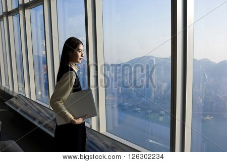 Asian skilled businesswoman is holding laptop computer while is standing in modern office interior near big window with cityscape view. Female executive looking satisfied after her successful meeting