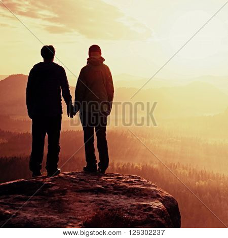 Couple In Love Enjoying Tender Moments During Sunset . Young Pair Of Hikers Hand In Hand On The Peak