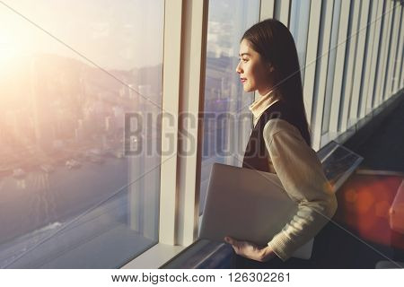 Young woman candidate is holding laptop computer while standing in office interior and looking out of big window with city view. Female manager with net-book in hand ponder about new business project