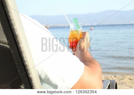 The man at the sea resting on a lounger with a cocktail