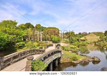 Stone bridge in Suizen-ji Joju-en garden at Kumamoto Prefecture, Kyushu, Japan. Suizenji Jojuen Park is a traditional Japanese garden landscaped around a natural spring pond.