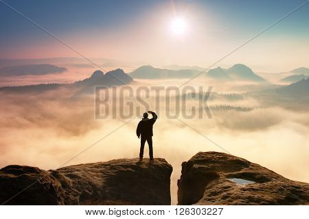 Colorful Misty Morning In Rocks. Tourist In Dark Cloths On Rock Empire Shadowing Eyes