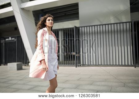Pretty girl stands on the background of the concrete wall and the metal fence. She wears the white dress with dots and the pink coat. She looks forward. Outdoors. Horizontal.