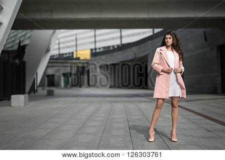 Pretty girl stands on the background of the concrete building. She wears the white dress with dots and the pink coat and shoes. She looks to the left and holds coat by her hands. Outdoors. Horizontal.
