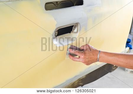 Auto body repair series : Closeup of hand working on putty