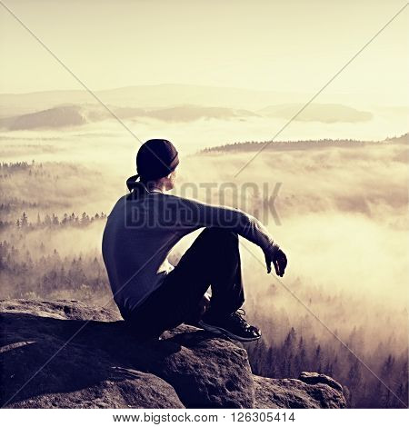 Man sit on the peak of rock and watching into colorful mist and fog in forest valley.