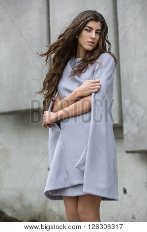 Stylish girl in the gray coat stands on the concrete wall background. She has the beautiful hair. She looks into the camera with parted lips. She clasped her body with hands which holds the coat. Outdoors. Vertical.