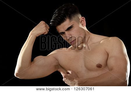young handsome sport man posing with strong naked torso looking cool and defiant with bent arm pointing biceps muscle in healthy lifestyle and gym club bodybuilding advertising concept