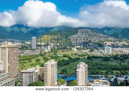 Waikiki, Honolulu, Hawaii, USA - Dec 15, 2015: Morning view of the Palolo region that backs against the distant hills, with dramatic cloud patterns. On the 30th floor of the Hyatt Regency Hotel.