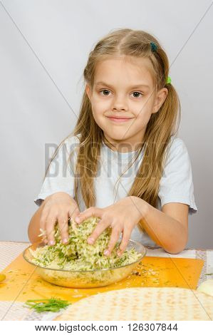 The Girl At The Kitchen Table With A Slight Smile Mixes Hands In A Bowl The Grated Cheese With Herbs