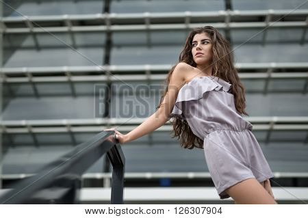 Pretty brunette with beautiful hair in the gray suit on the background of the metal-glass constructions. She holds her right hand on the black hand-rail. She looks to the right. Outdoors. Horizontal.